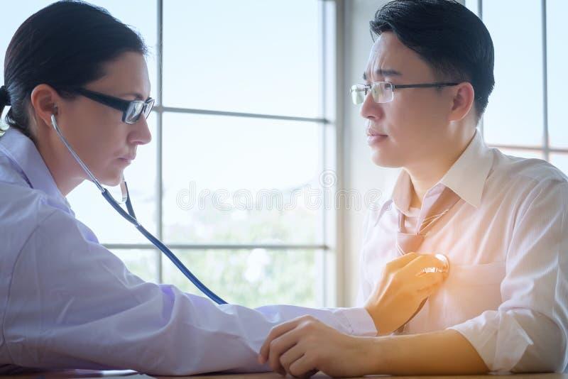 Starsza kobiety lekarka konsultuje młodego Cierpliwego obsiadanie przy lekarką obraz royalty free