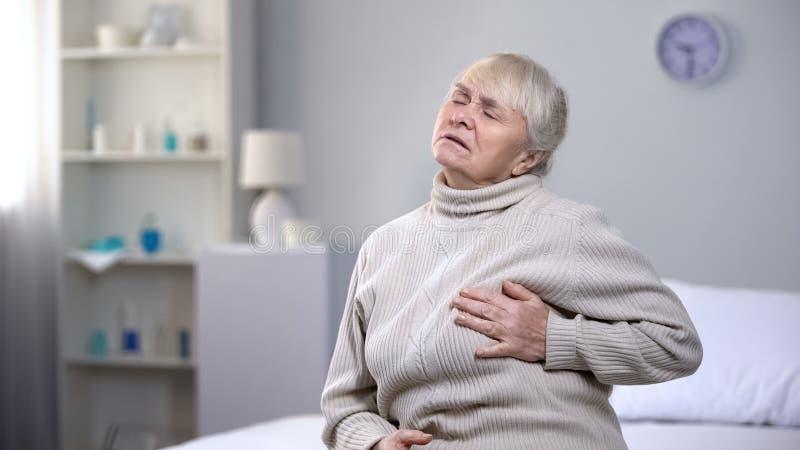 Starsza kobiety mienia klatka piersiowa, nagle czuje atak serca, problemy zdrowotni zdjęcie stock