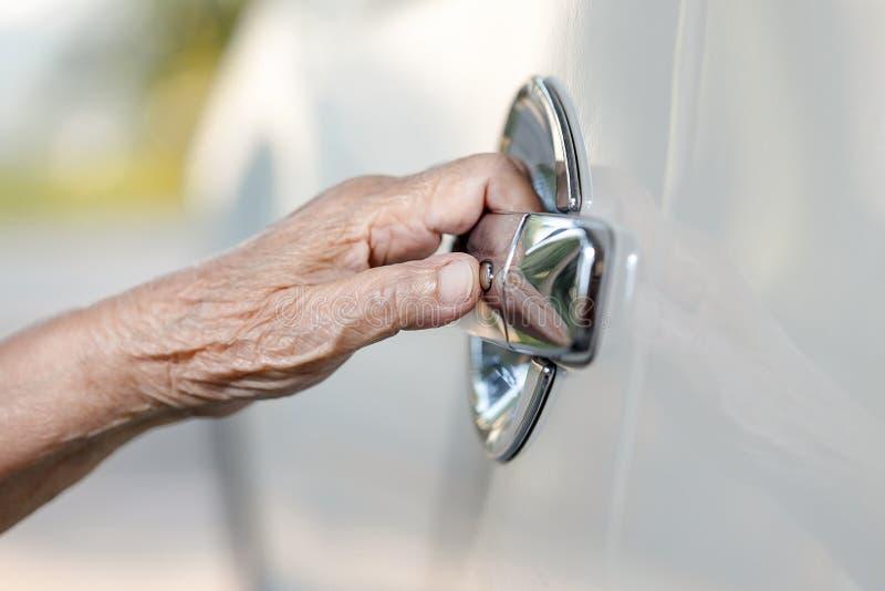 Starsza kobiety ręka otwiera samochodowego drzwi zdjęcie royalty free