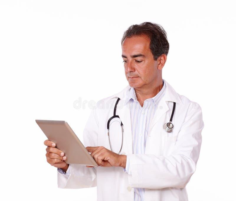 Starsza latynos lekarka używa jego pastylka komputer osobistego obrazy stock