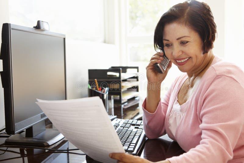 Starsza Latynoska kobieta pracuje na komputerze w domu fotografia stock