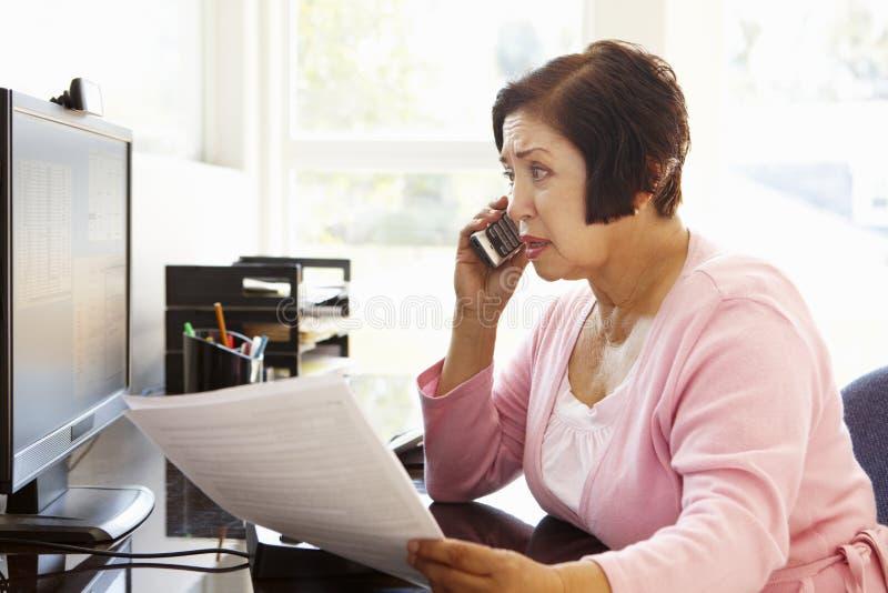 Starsza Latynoska kobieta pracuje na komputerze w domu fotografia royalty free