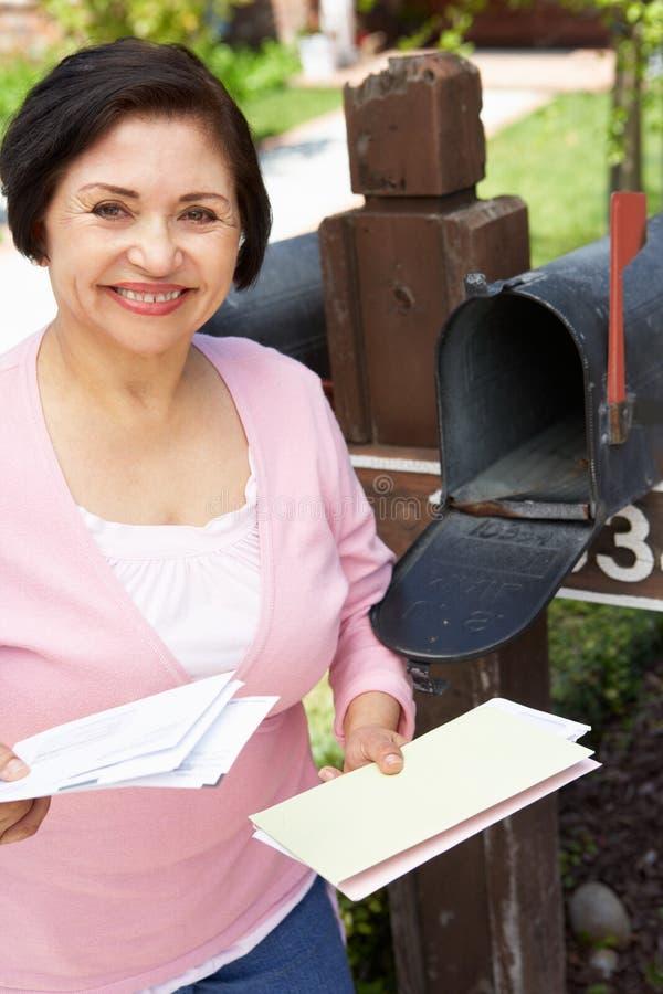Starsza Latynoska kobieta Sprawdza skrzynkę pocztowa zdjęcie royalty free