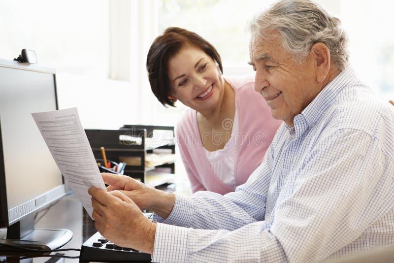 Starsza Latynoska para pracuje na komputerze w domu zdjęcia royalty free