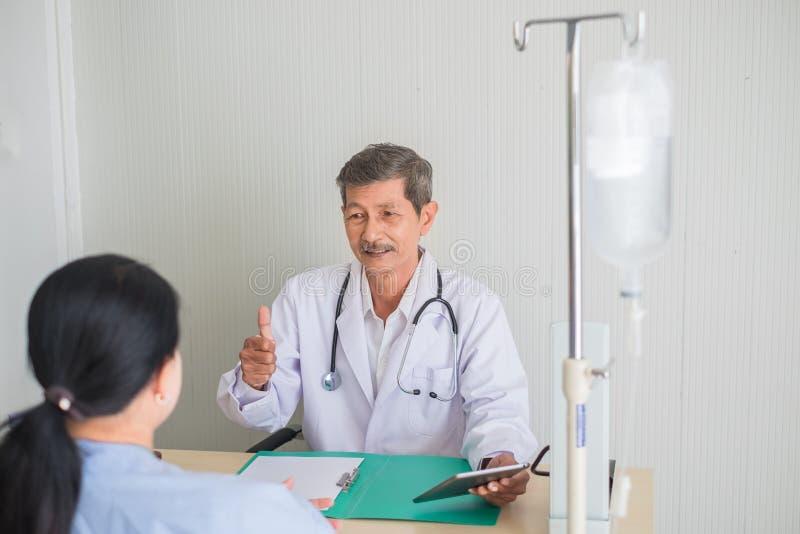 Starsza lekarka podnosz?cy azjaty palec, spojrzenie przy ?e?skim pacjentem z u?miechem i obraz royalty free