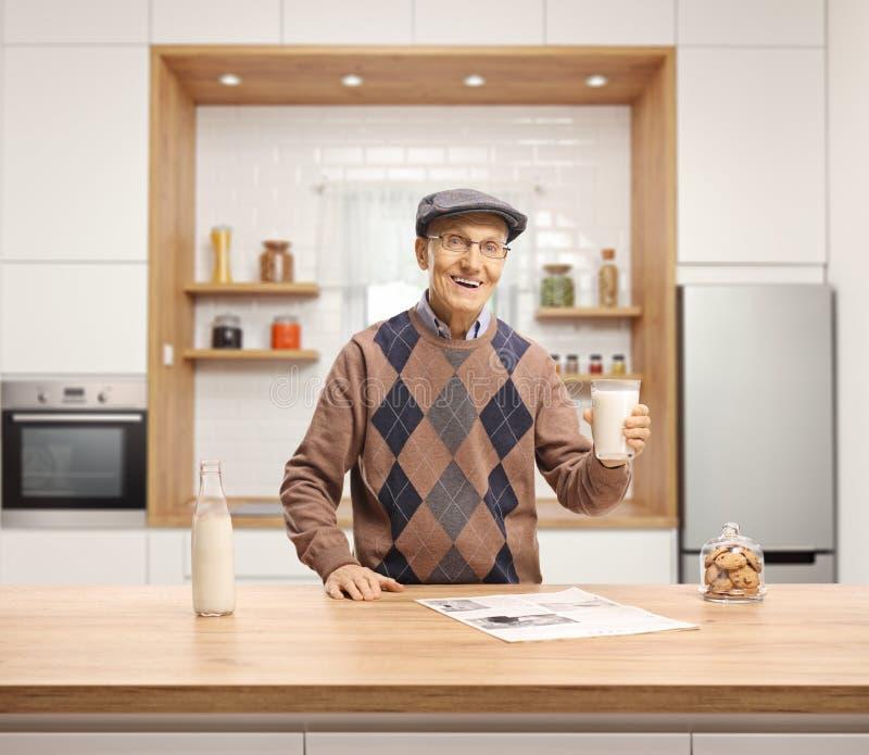 Starsza osoba mężczyzna trzyma szkło mleko i pozycja za drewnianym kontuarem w kuchni obrazy stock