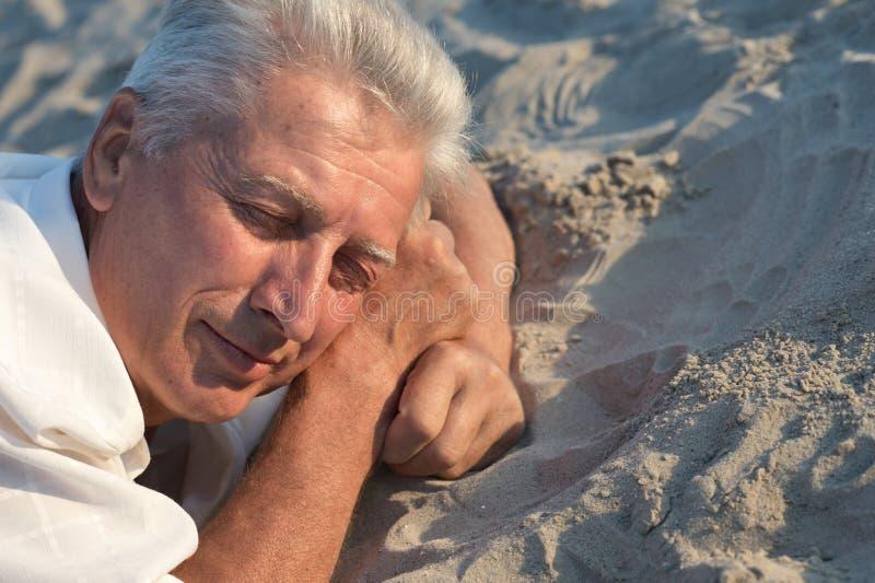Starsza osoba mężczyzna dosypianie na piasku obraz stock