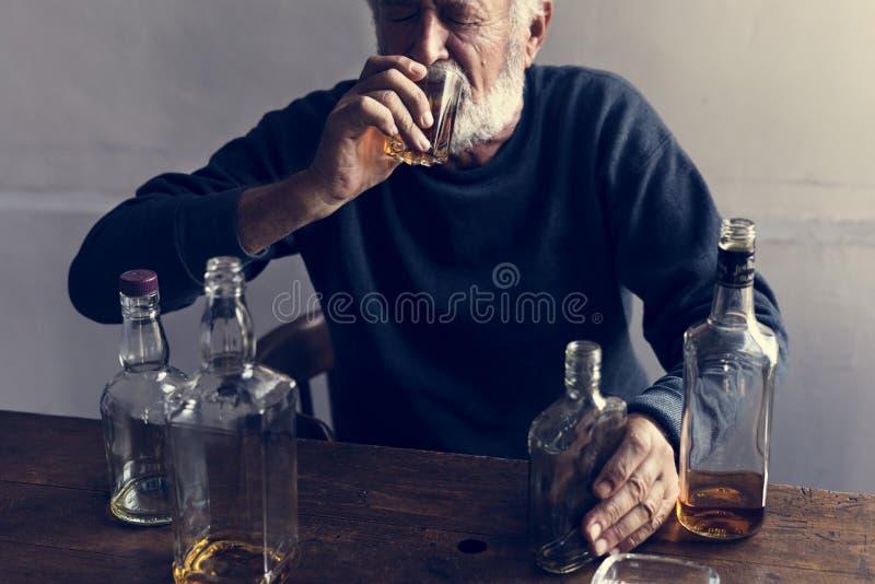 Starsza osoba mężczyzna obsiadanie pije whisky alkoholicznego nałogu złego przyzwyczajenie fotografia stock