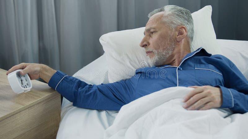 Starsza osoba mężczyzna przesłuchania budzik, niechętny budził się, brak sen i energia fotografia royalty free