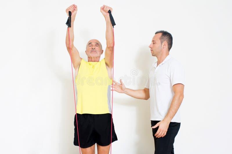 Starsza osoba mężczyzna rozciąganie przed osobistym trenerem obrazy royalty free