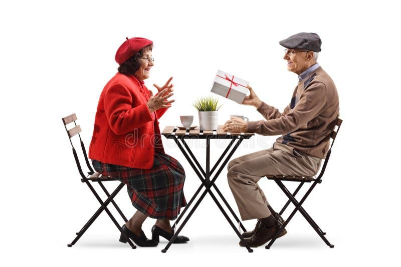 Starsza osoba mężczyzny obsiadanie przy kawiarnią i dawać teraźniejszości starsza kobieta zdjęcie royalty free