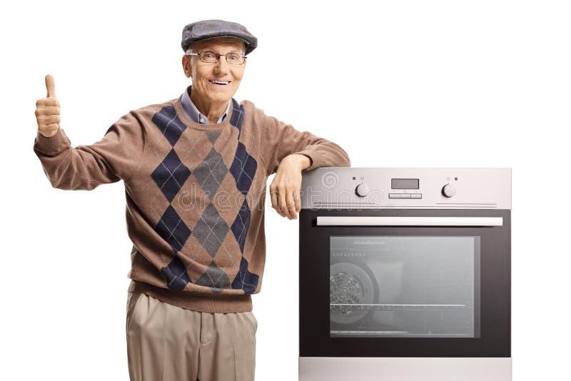 Starsza osoba mężczyzny pozycja z elektrycznym piekarnikiem i dawać aprobatami fotografia royalty free