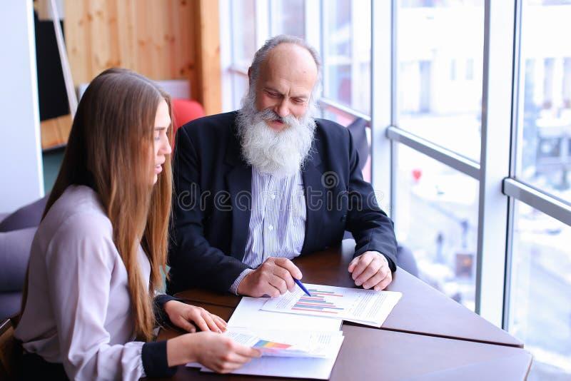 Starsza osoba szefa mężczyzna znaków dokument z młodym asystentem z papierami zdjęcie stock