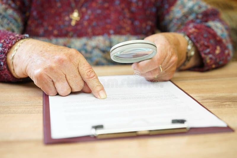 Starsza osoba z powiększać - szklany sprawdza dokument obraz stock