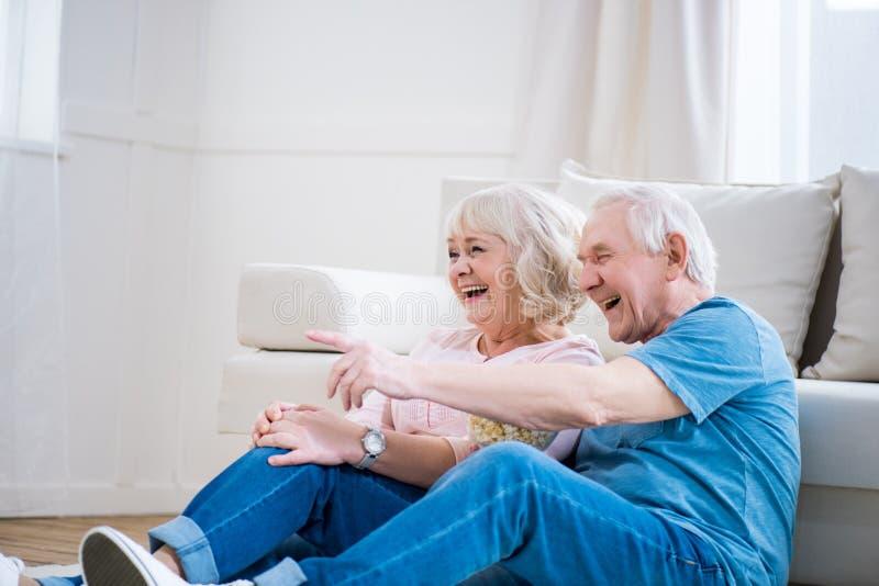 Starsza para śmia się i siedzi na podłoga, mężczyzna wskazywać fotografia royalty free