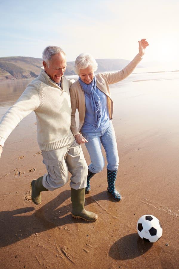 Starsza para Bawić się futbol Na zimy plaży zdjęcie royalty free