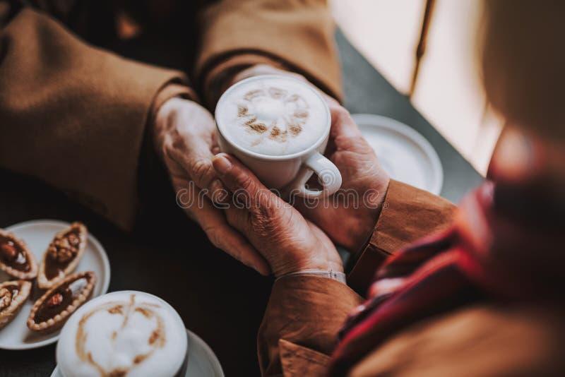 Starsza para cieszy się cappuccino z latte sztuką przy kawiarnią zdjęcie stock