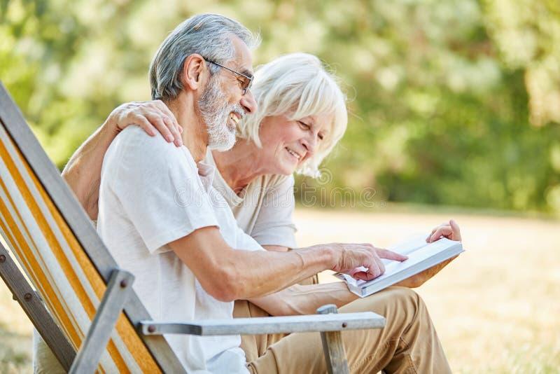 Starsza para czyta książkę wpólnie zdjęcia stock