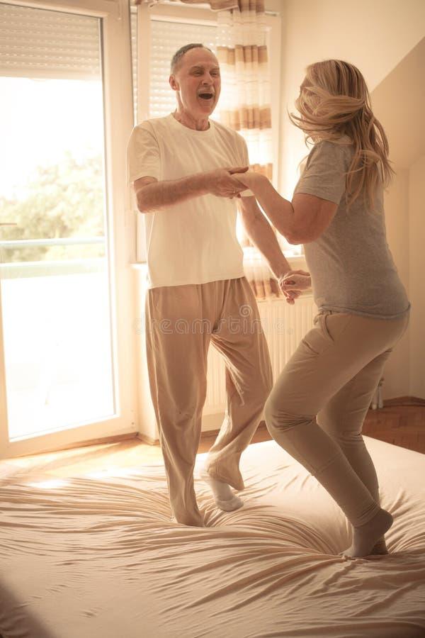 Starsza para ma zabawę na łóżku obraz royalty free