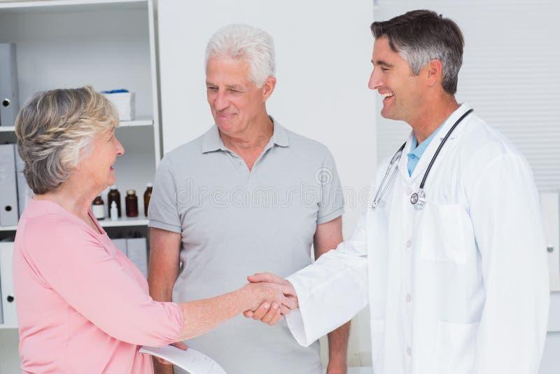 Starsza para ono uśmiecha się podczas gdy odwiedzający lekarkę zdjęcie royalty free