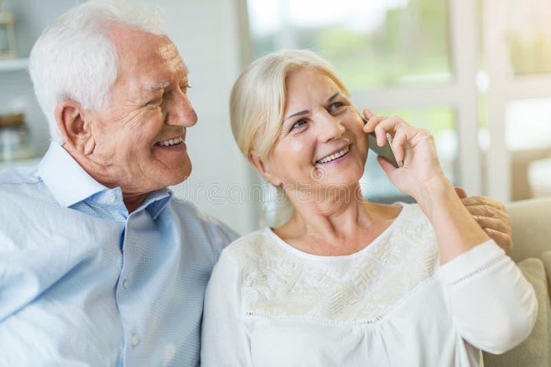 Starsza para opowiada na telefonie komórkowym w domu zdjęcia royalty free