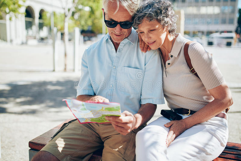 Starsza para patrzeje dla miejsca przeznaczenia na miasto mapie zdjęcia stock