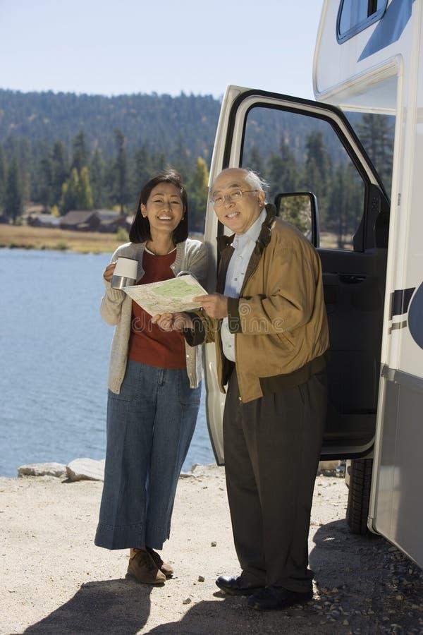 Starsza para patrzeje mapę na zewnątrz RV przy jeziorem fotografia stock