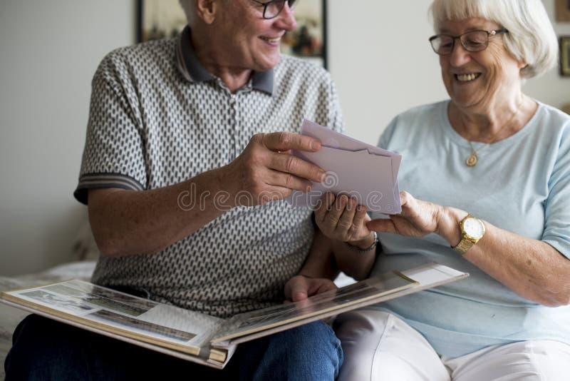 Starsza para patrzeje rodzinnego album fotograficznego zdjęcia stock