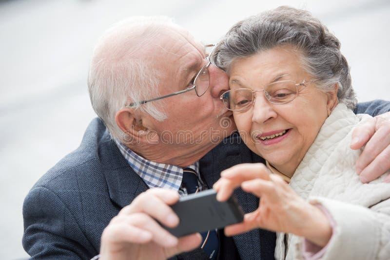 Starsza para pokazuje jaźń portreta fotografię na smartphone fotografia stock