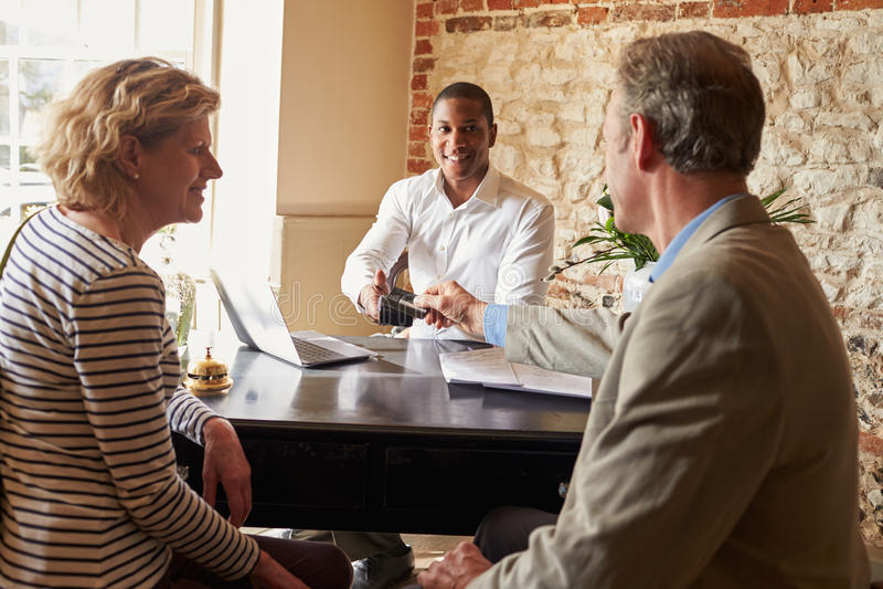 Starsza para robi kredytowej karty zapłacie przy hotelowym sprawdza wewnątrz zdjęcie royalty free