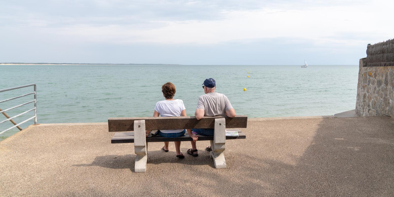 Starsza para spoglądająca na morze na ławkę na plaży vendee France w formie baneru internetowego obraz stock