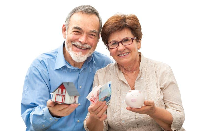 Starsza para trzyma domowego prosiątko banka i modela zdjęcia stock