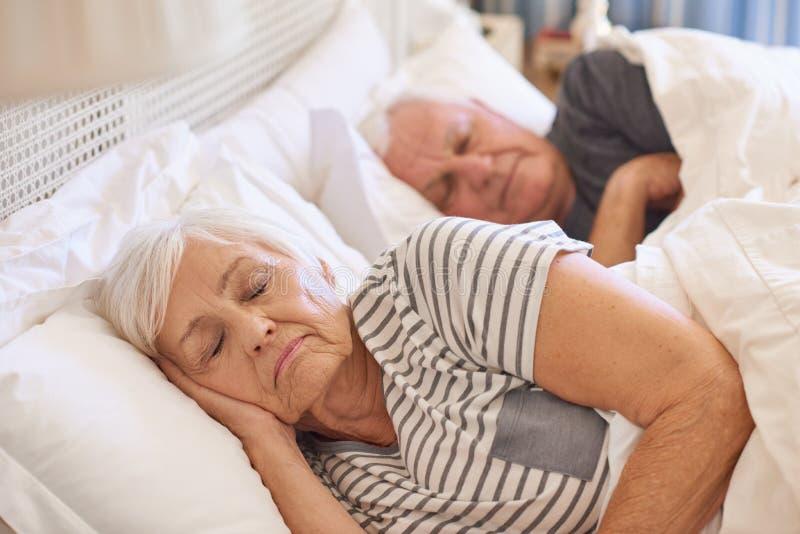 Starsza para uśpiona w ich łóżku w domu obrazy royalty free