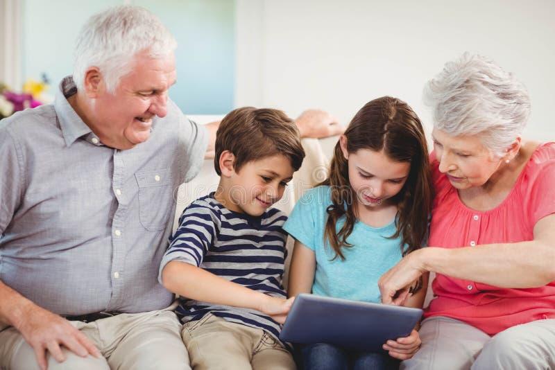 Starsza para używa cyfrową pastylkę z ich uroczystymi dziećmi obraz stock