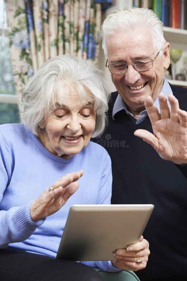 Starsza para Używa Cyfrowej pastylkę Dla wideo wezwania Z rodziną obraz stock