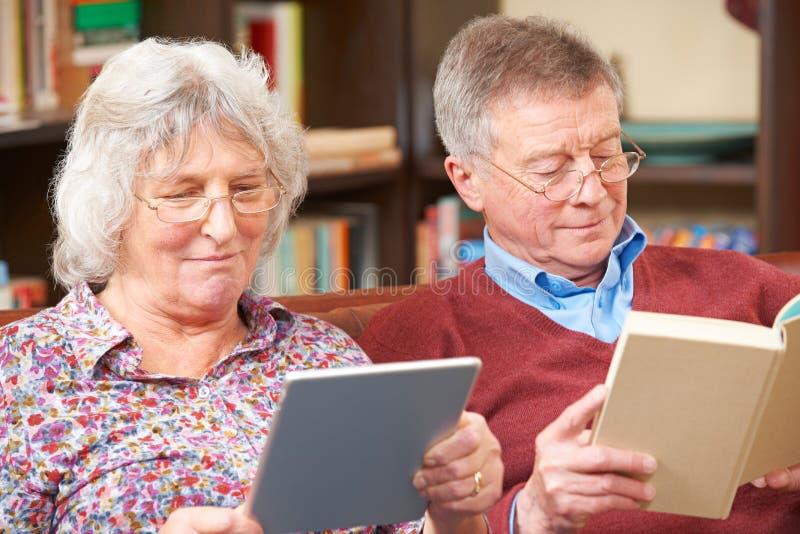 Starsza para Używa Cyfrowej pastylkę I Czytelniczą książkę obrazy royalty free