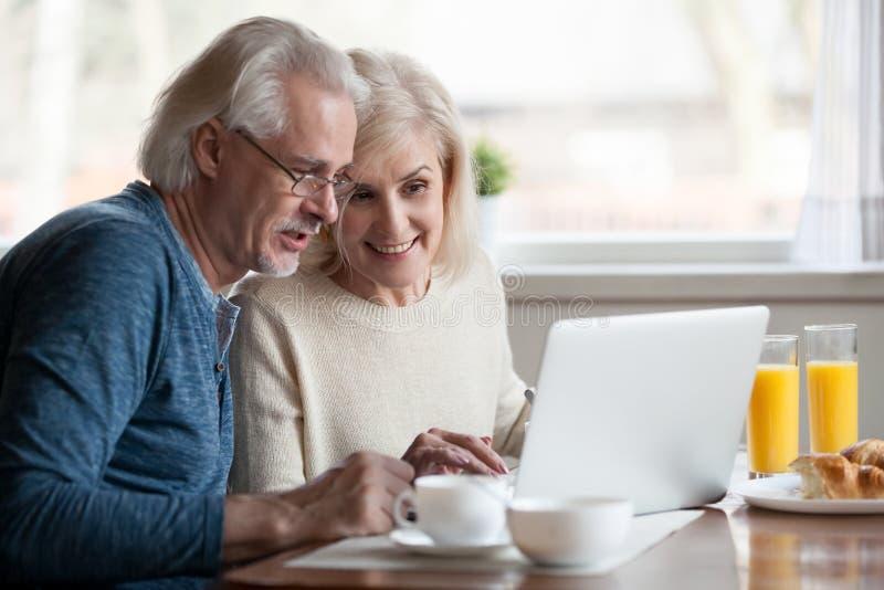 Starsza para używa laptop podczas gdy mieć śniadanie w domu obraz stock