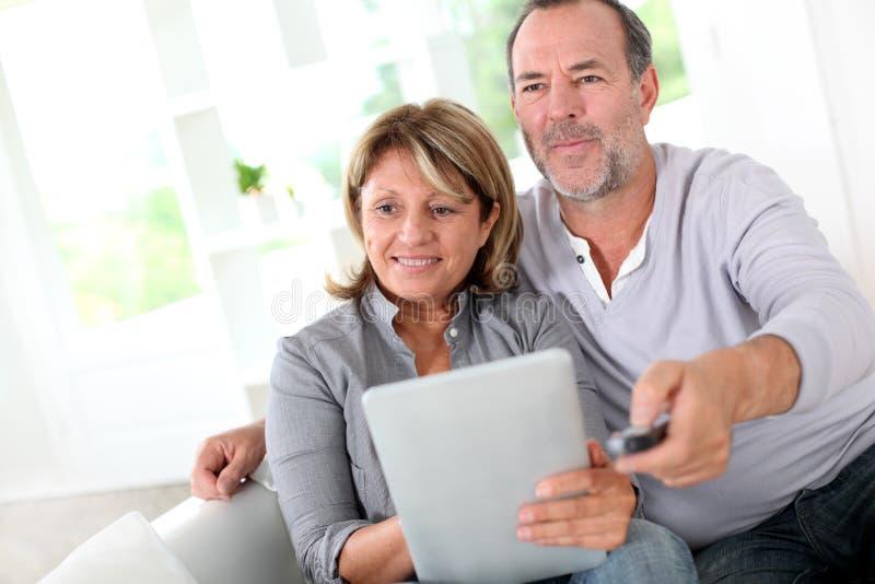 Starsza para używa pastylkę i oglądający tv fotografia stock