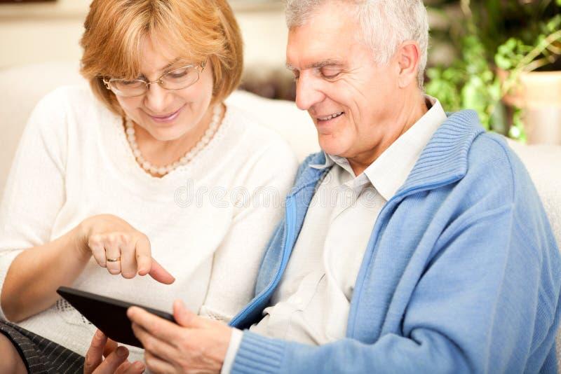 Starsza para używa pastylka peceta zdjęcia royalty free