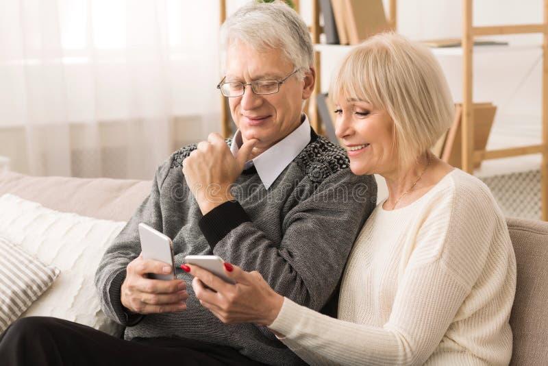 Starsza para używa smartphones, ogląda fotografie w domu zdjęcie stock