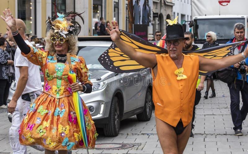 2019: Starsza para uczęszcza Gay Pride w wyśmienitych pomarańczowych kostiumach paraduje także zna jako Christopher Uliczny dzień obraz royalty free