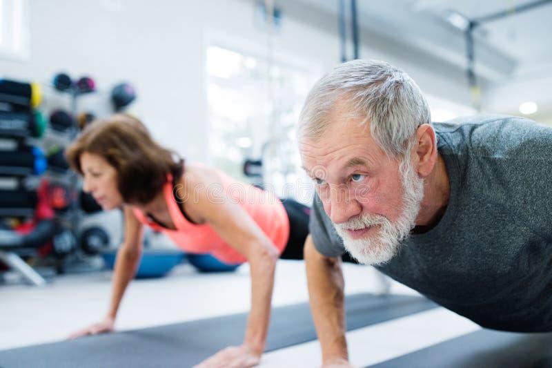 Starsza para w gym pracującym out, robić pcha podnosi fotografia stock