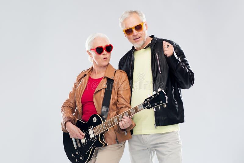 Starsza para w okularach przeciwsłonecznych z gitarą elektryczną zdjęcia stock