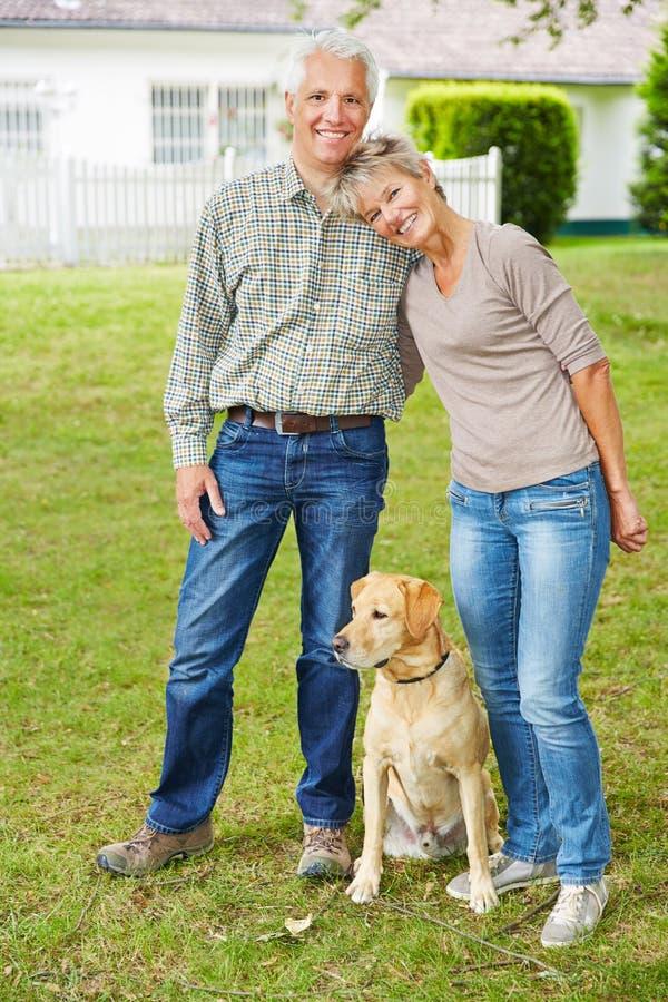 Starsza para z psem przed domem fotografia royalty free