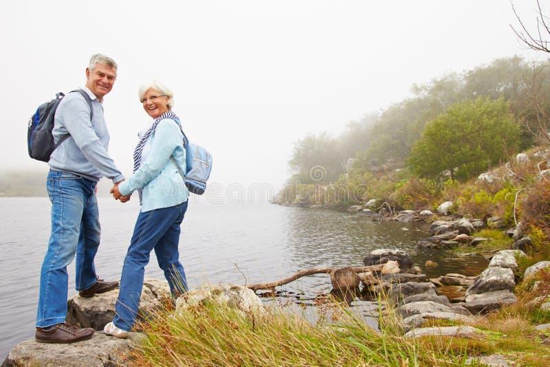 Starsza pary pozycja jeziorem, ono uśmiecha się kamera obraz stock