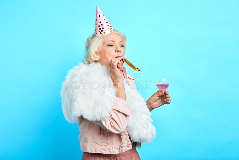 Starsza piękna kobieta dmucha partyjnego róg fotografia stock