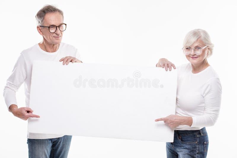 Starsza piękna para z pustą białą deską obraz royalty free