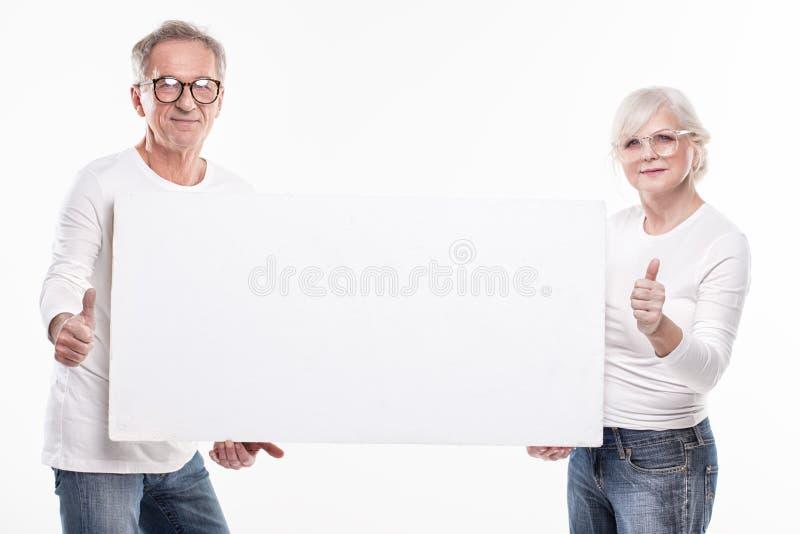 Starsza piękna para z pustą białą deską zdjęcia royalty free