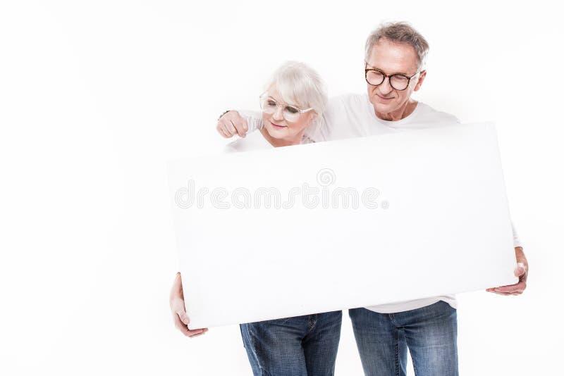Starsza piękna para z pustą białą deską fotografia royalty free