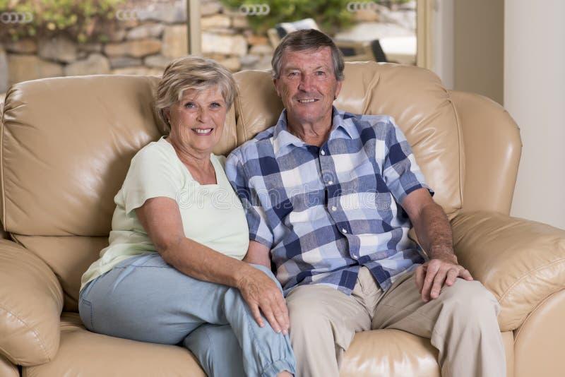 Starsza piękna wiek średni para uśmiecha się szczęśliwego żyje izbowej kanapy leżanki przyglądającego cukierki w życiu wpólnie w  zdjęcie stock